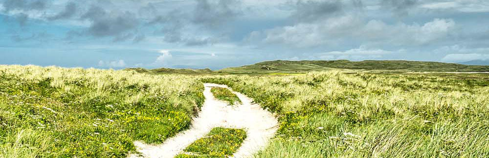 a path cut into sand dunes below a cloudy blue sky on the Island of Uist
